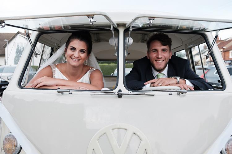 bride and groom looking through front windows of camper van
