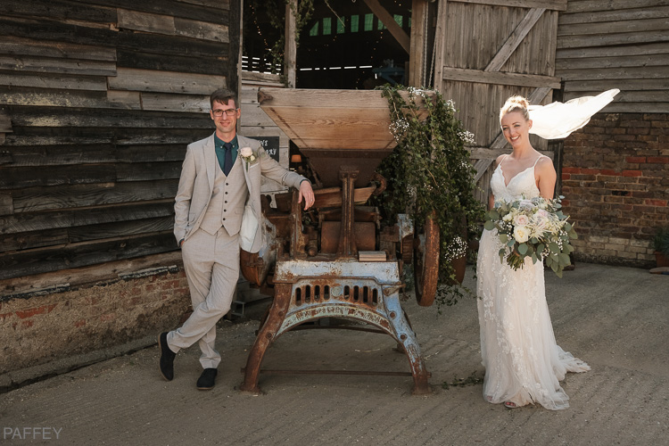 cool looking bride and groom in front of barns