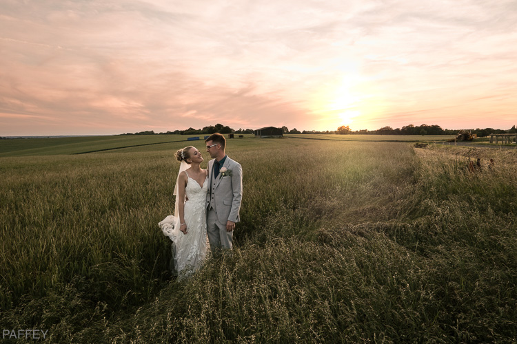 sunset wedding photographed in a field