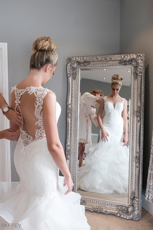 bride in her wedding dress looking into a mirrow