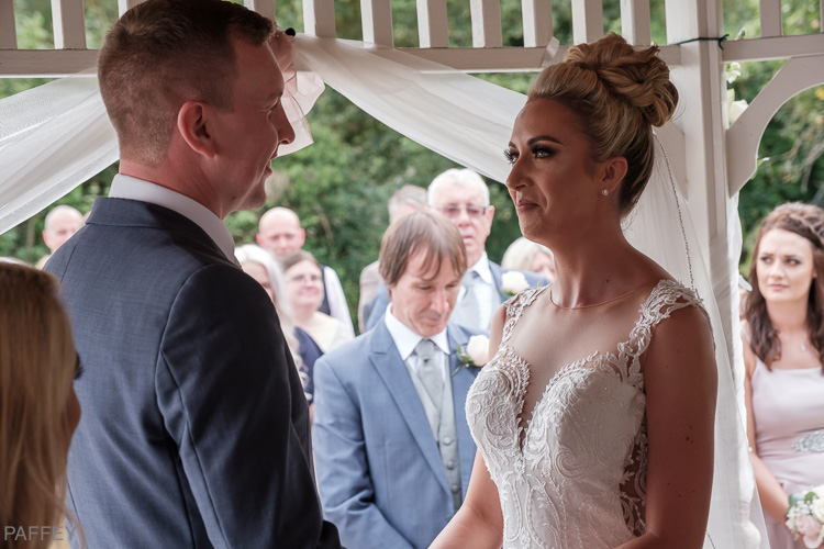 bride and groom getting married in a gazebo