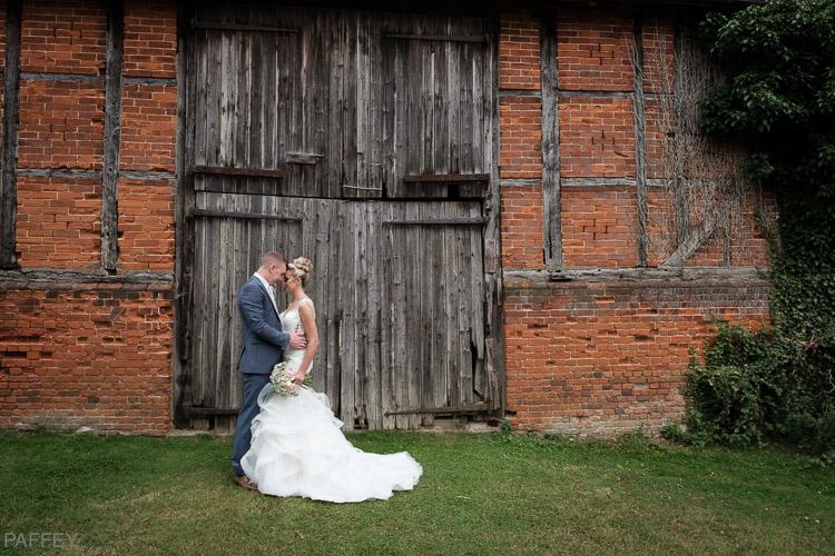 bride and groom in front of a barn door