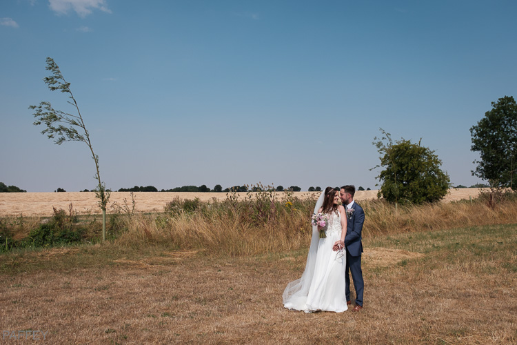 bride and groom in a field country style wedding