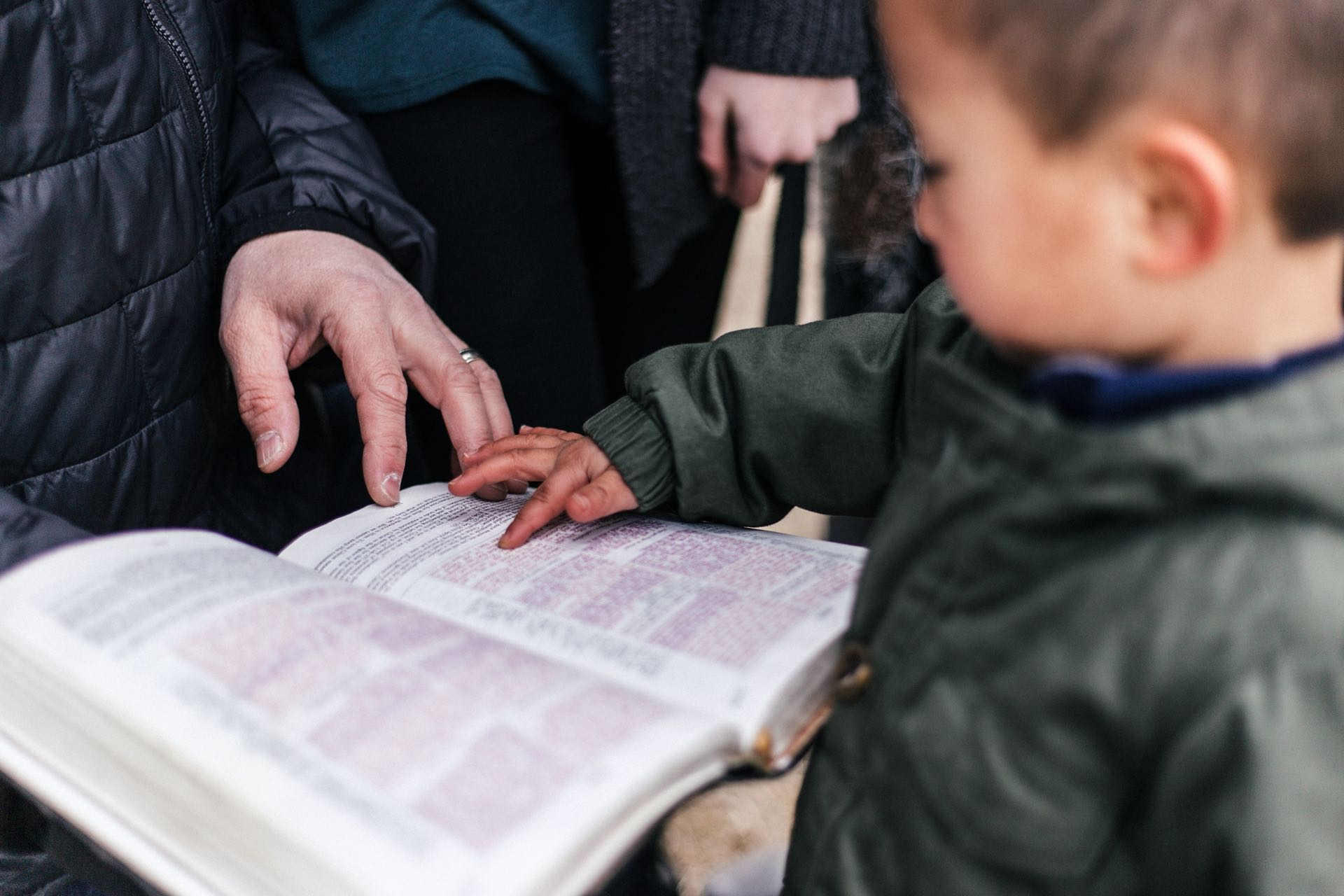 Small child pointing to a verse in the Bible with adult holding the book
