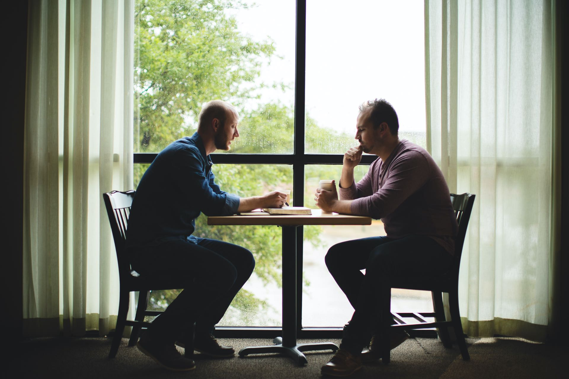 Two men at a table having a conversation over coffee