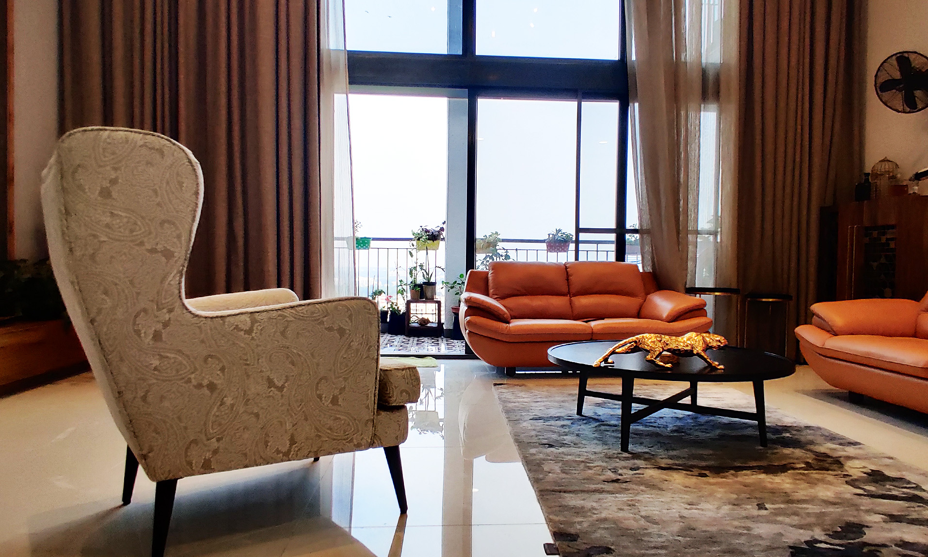 Double height living room in a penthouse apartment in Bangalore , with a highbacked chair as the center of the room