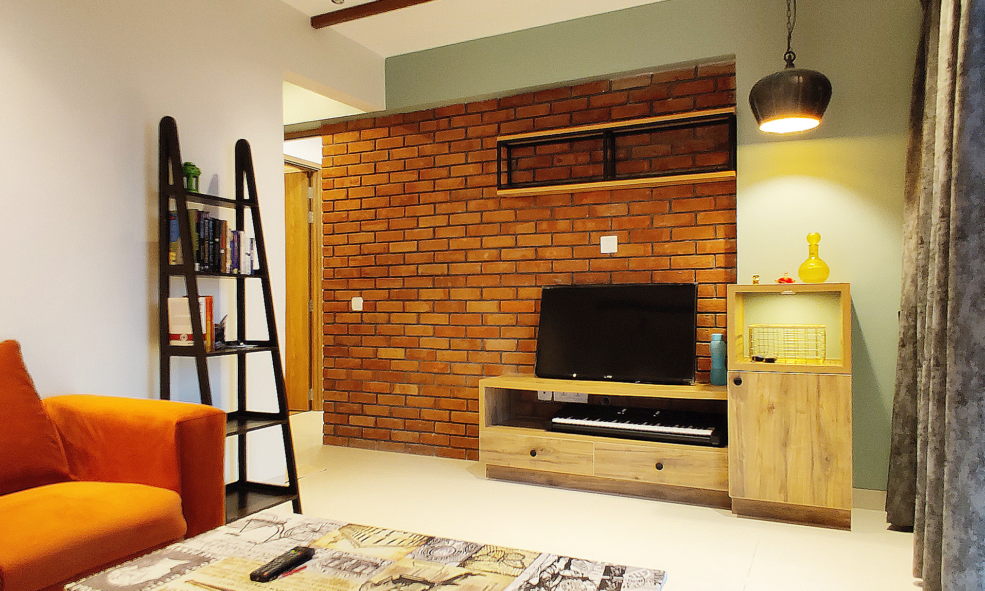 tv unit with brick cladding on wall and droplight