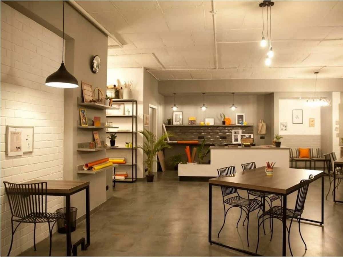 A casual worktables space with work tables, droplight, brick cladding, book shelves and warm yellow lights