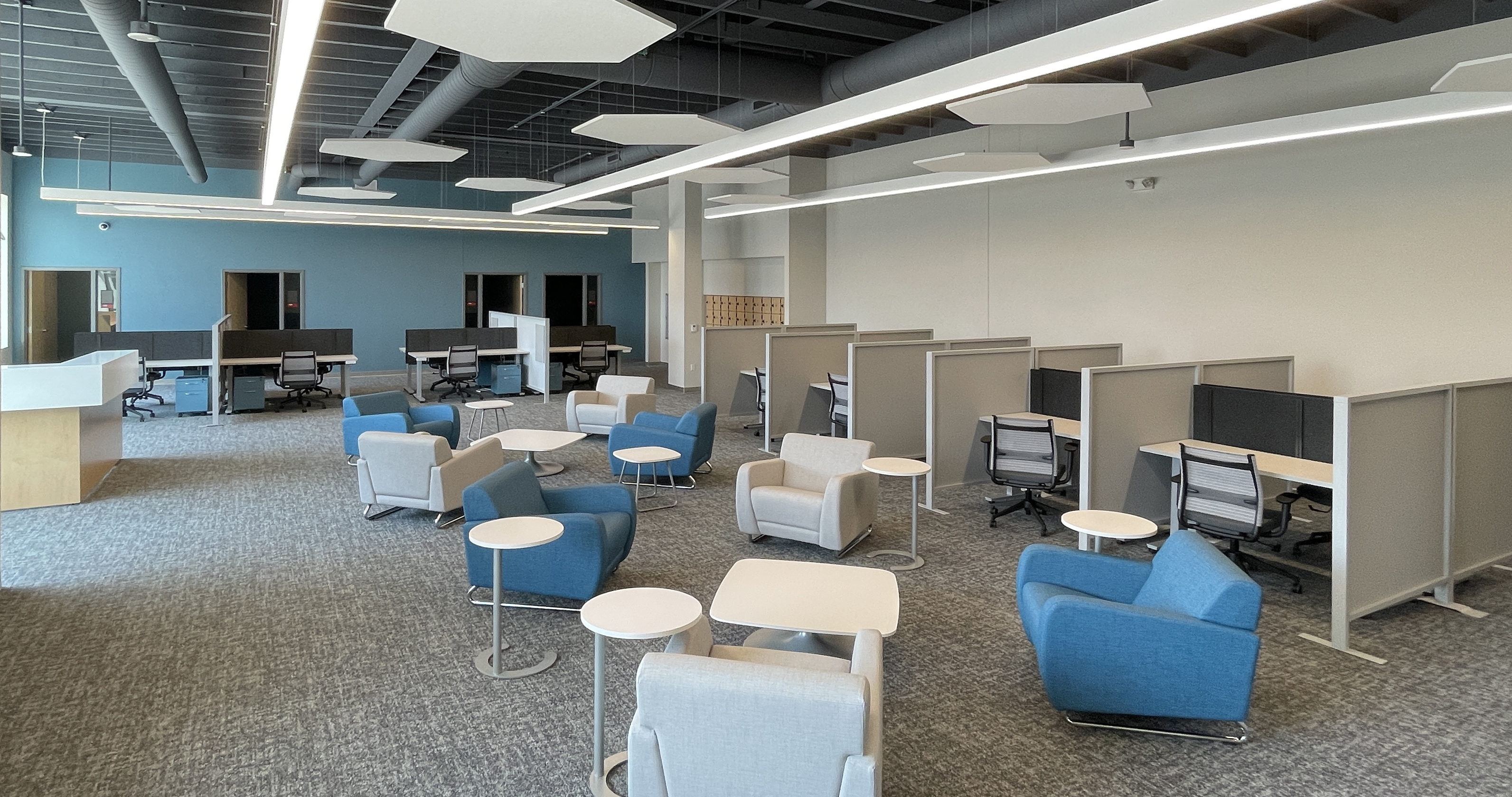 Photo of interior of the IGNITE space Large Blue Green wall with grey carpet Grey and black work stations and large Blue Green and Grey comfy chairs set around low tables