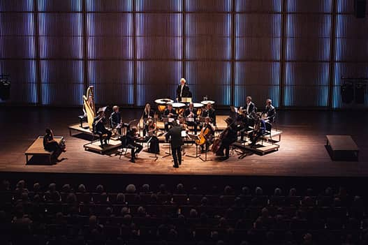 full stage with spotlight of a complete orchestra playing. audience is watching in the foreground.