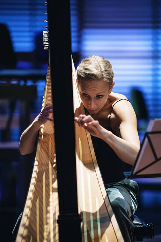 close up of doriene marselje playing the harp. Spot light shining on her from the top right and blurry background