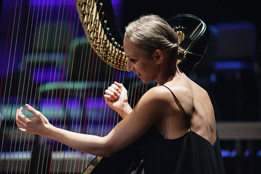 profile shot of dorience marselje playing the harp. light is shing on her with a dark background