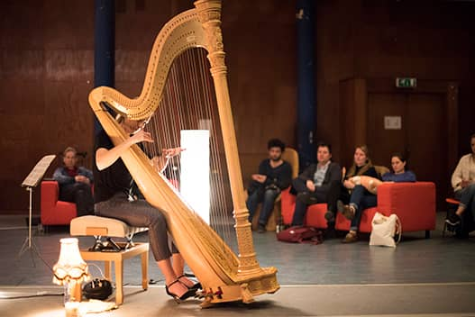 landscape photo of doriene Marselje playing the harp solo on the stage with audience in the background.