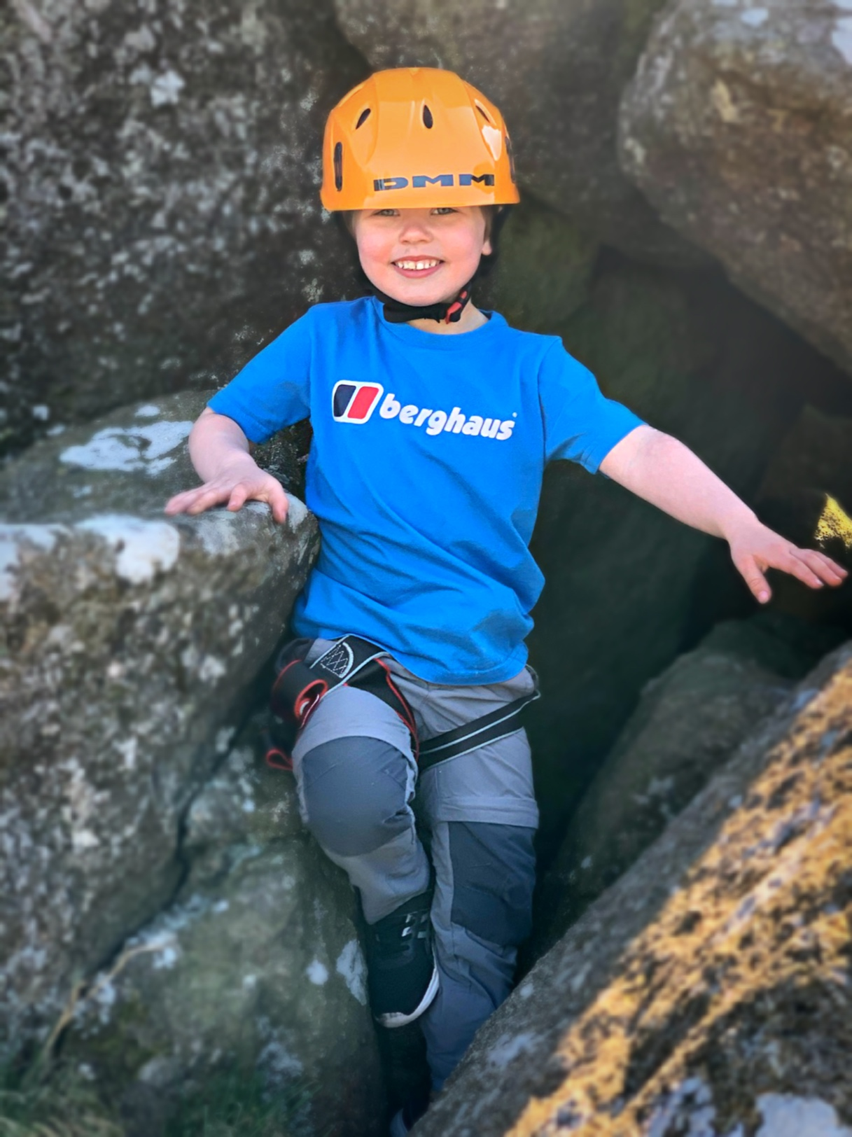young boy in climbing gear smiling at introduction to rockclimbing day with inaccessible solutions