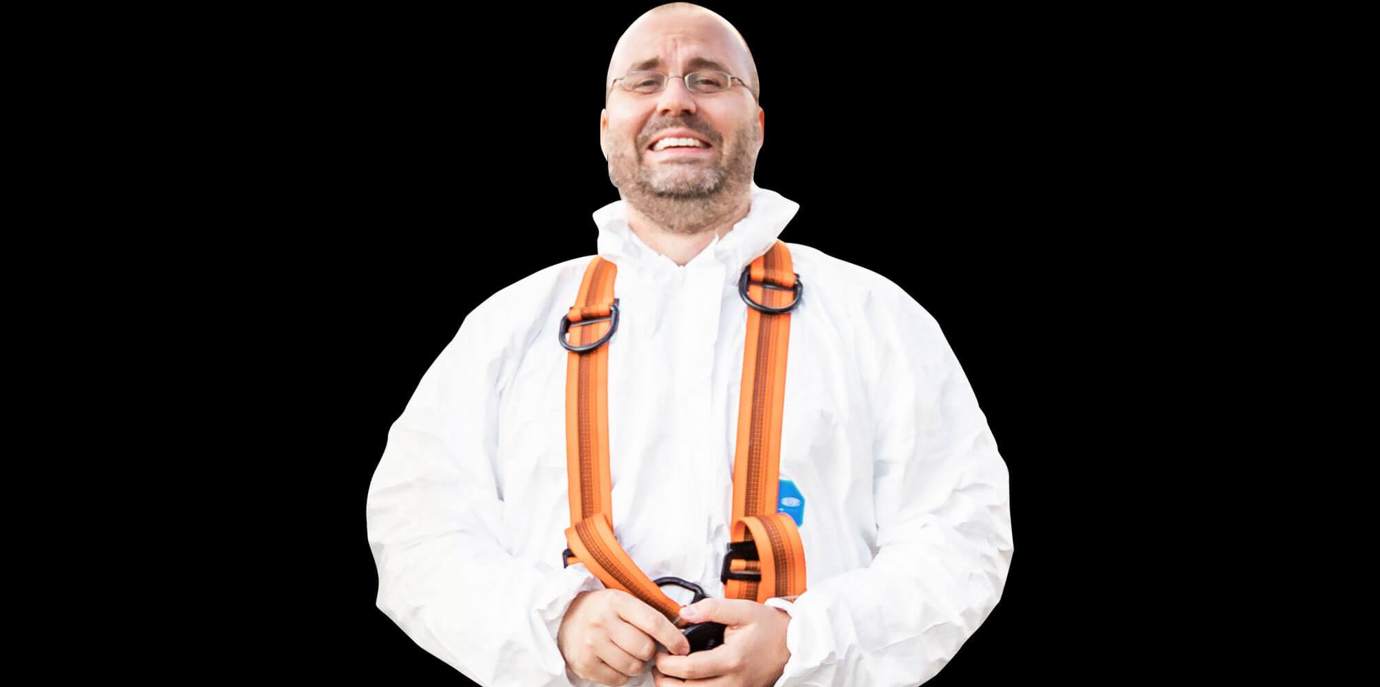 Matthias Gottwald trägt einen weißen Schutzanzug bei einem Videodreh für eine Kanalreinigungs-Firma und lacht in die Kamera.