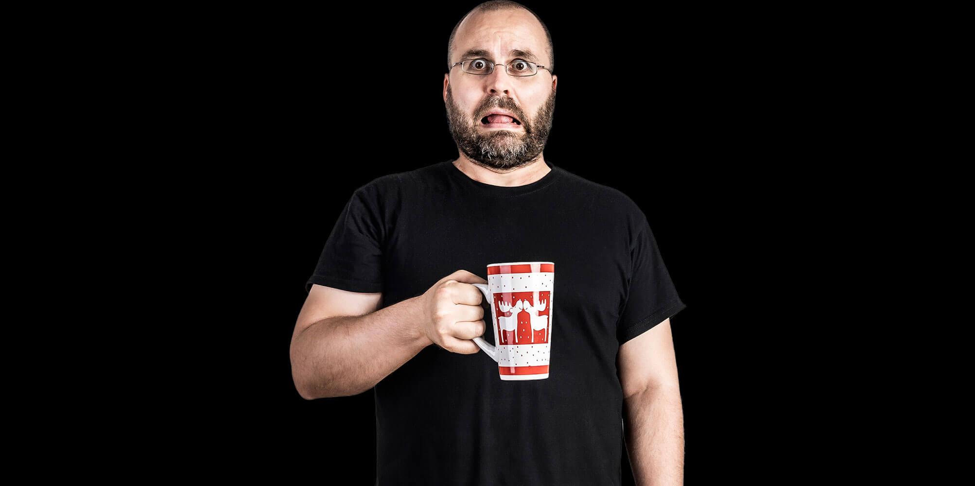 Matthias Gottwald hat eine Kaffeetasse in der Hand und zieht eine lustige Grimasse.