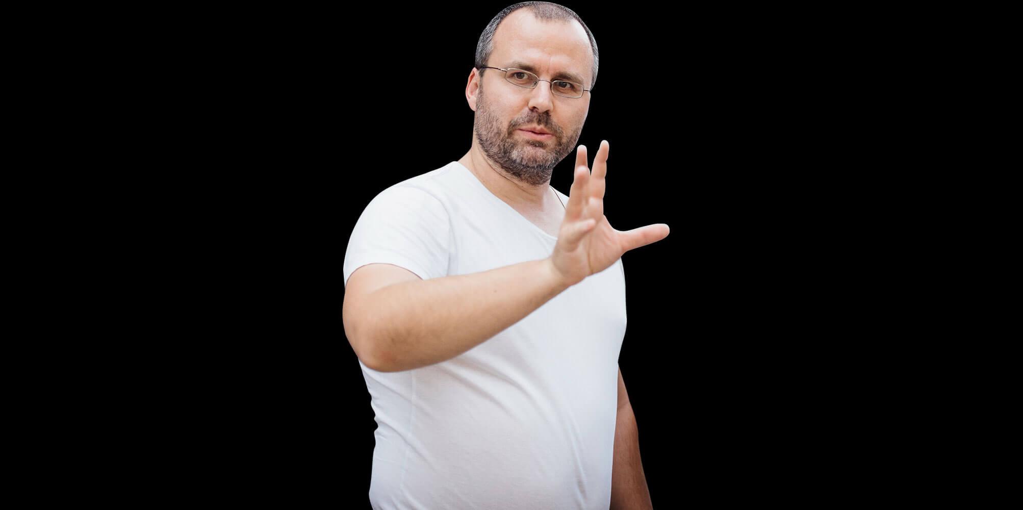 Matthias Gottwald macht im weißen T-Shirt eine Geste mit der Hand.
