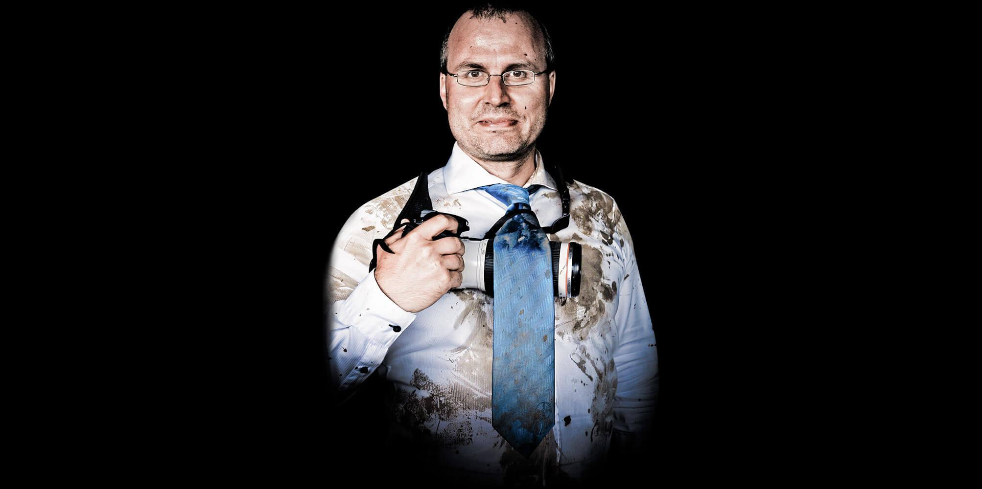 Matthias Gottwald mit feinem Hemd und Krawatte, die aber voller Schlamm sind.