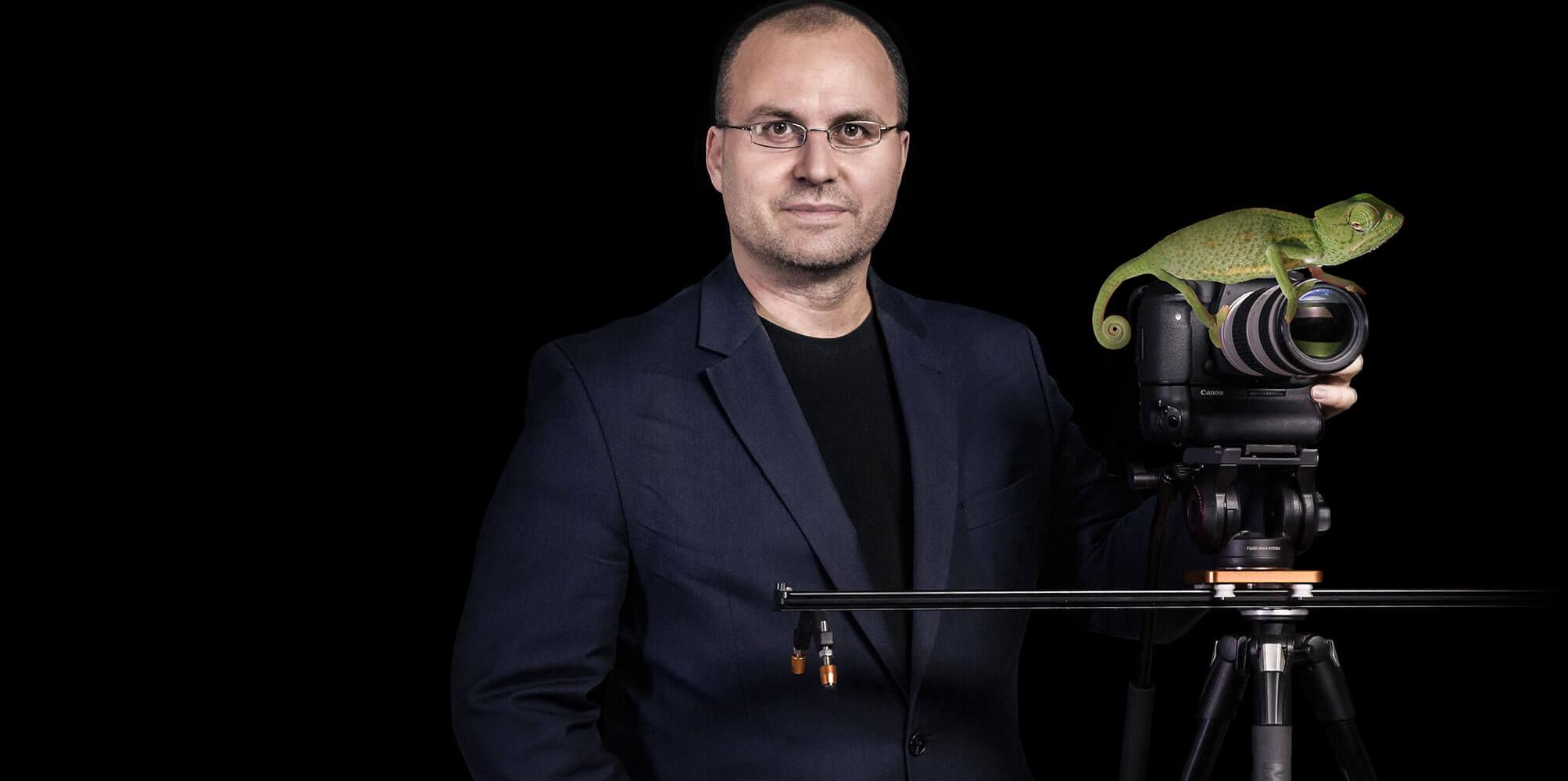 Matthias Gottwald steht neben der Kamera, auf der ein Chamäleon sitzt.