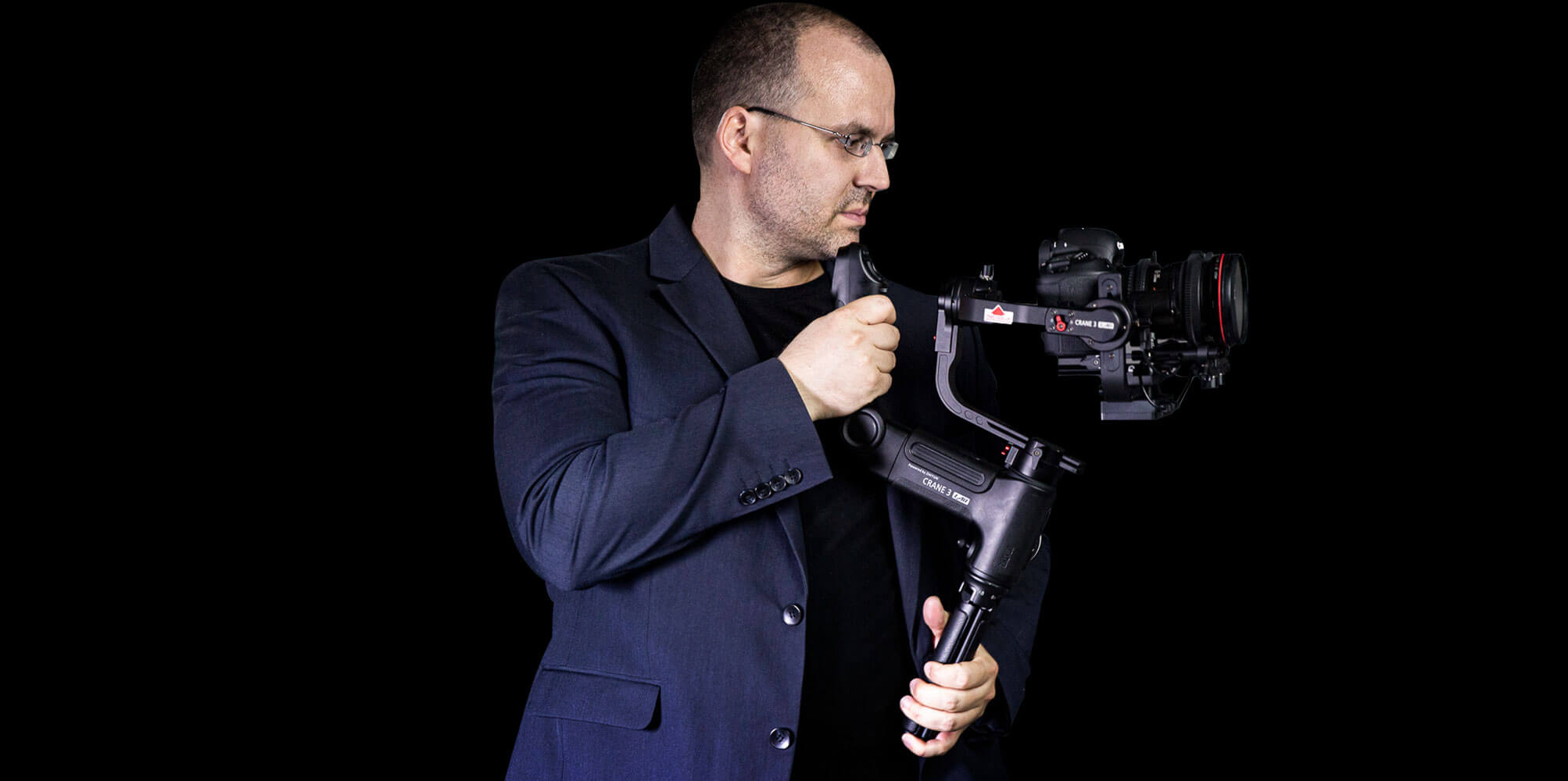 Matthias Gottwald von der Seite mit einer Videokamera und einem Gimbal zum Stabilisieren der Aufnahmen.
