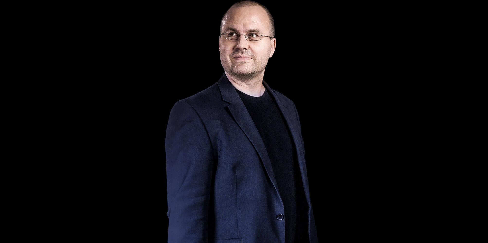 Matthias Gottwald trägt Sakko, lächelt und schaut nach oben links.
