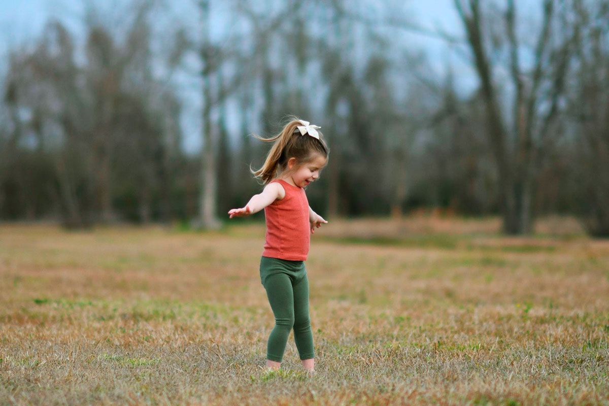 kid dancing in the middle of a field