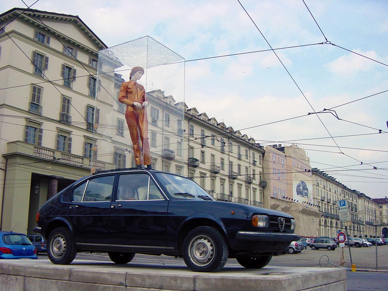 foto van Greta Blok pop in vitrine. bovenop een Alfa Romeo Alfasud. In Turijn