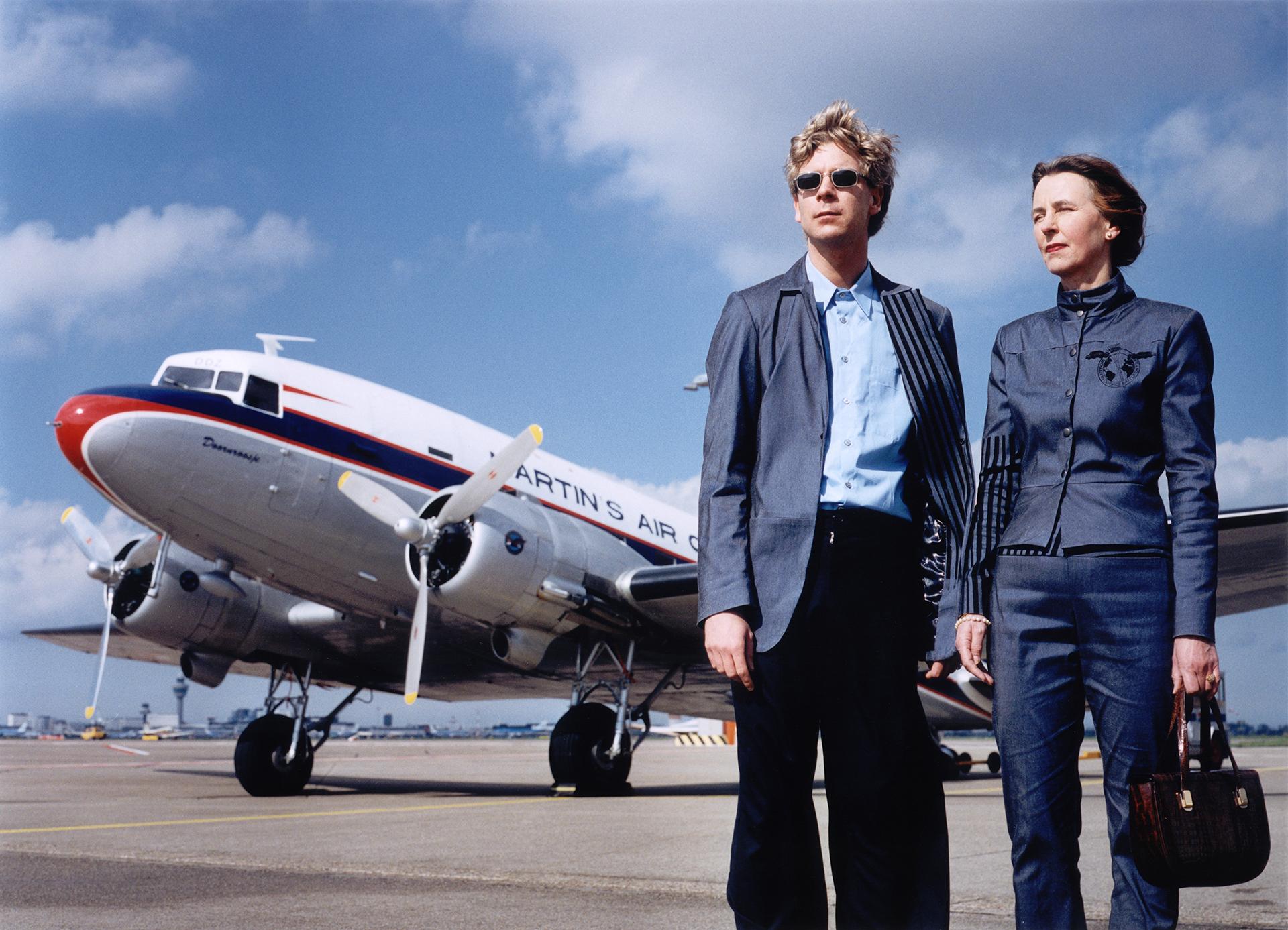 Photo from Cees Krijnen and Greta Blok wearing Woman in Divorce battle suits, 2000. Schiphol Amsterdam, met een Dakota genaamd 'Doornroosje' op de achtergrond.