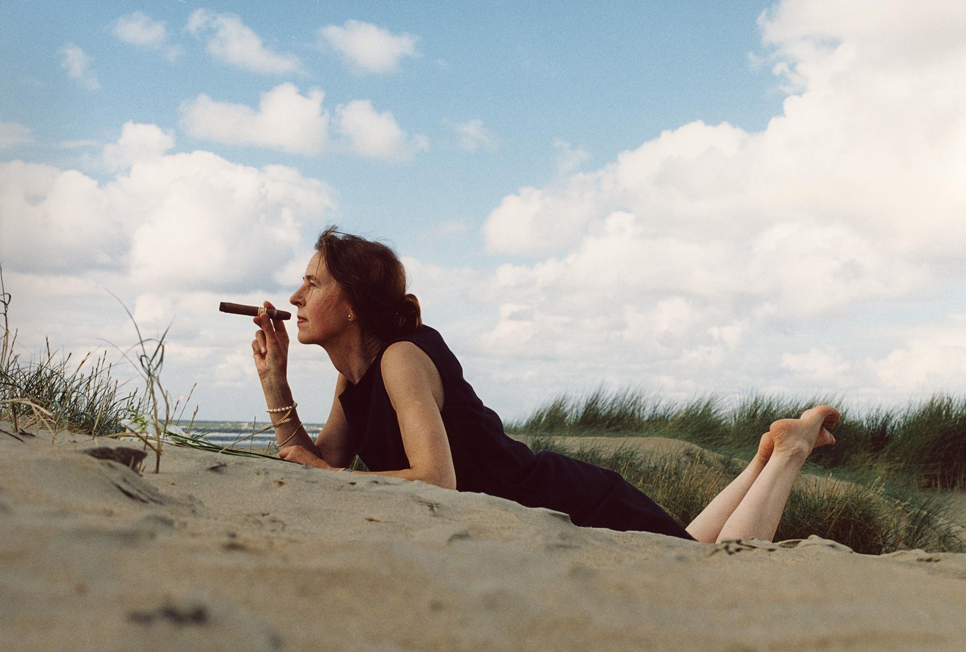 foto van sigaar rokende Greta Blok in duinpan met zee op achtergrond