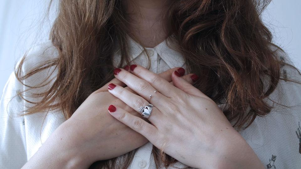 Frau mit Händen auf dem Herzen