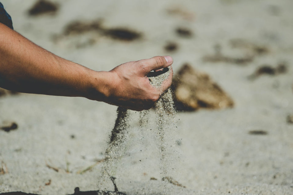 Sand fließt aus Hand