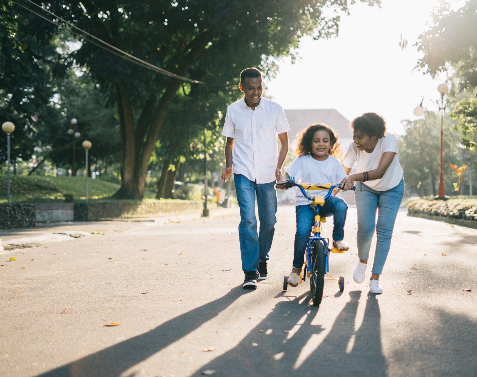 Parents run alongside their child riding a bike.