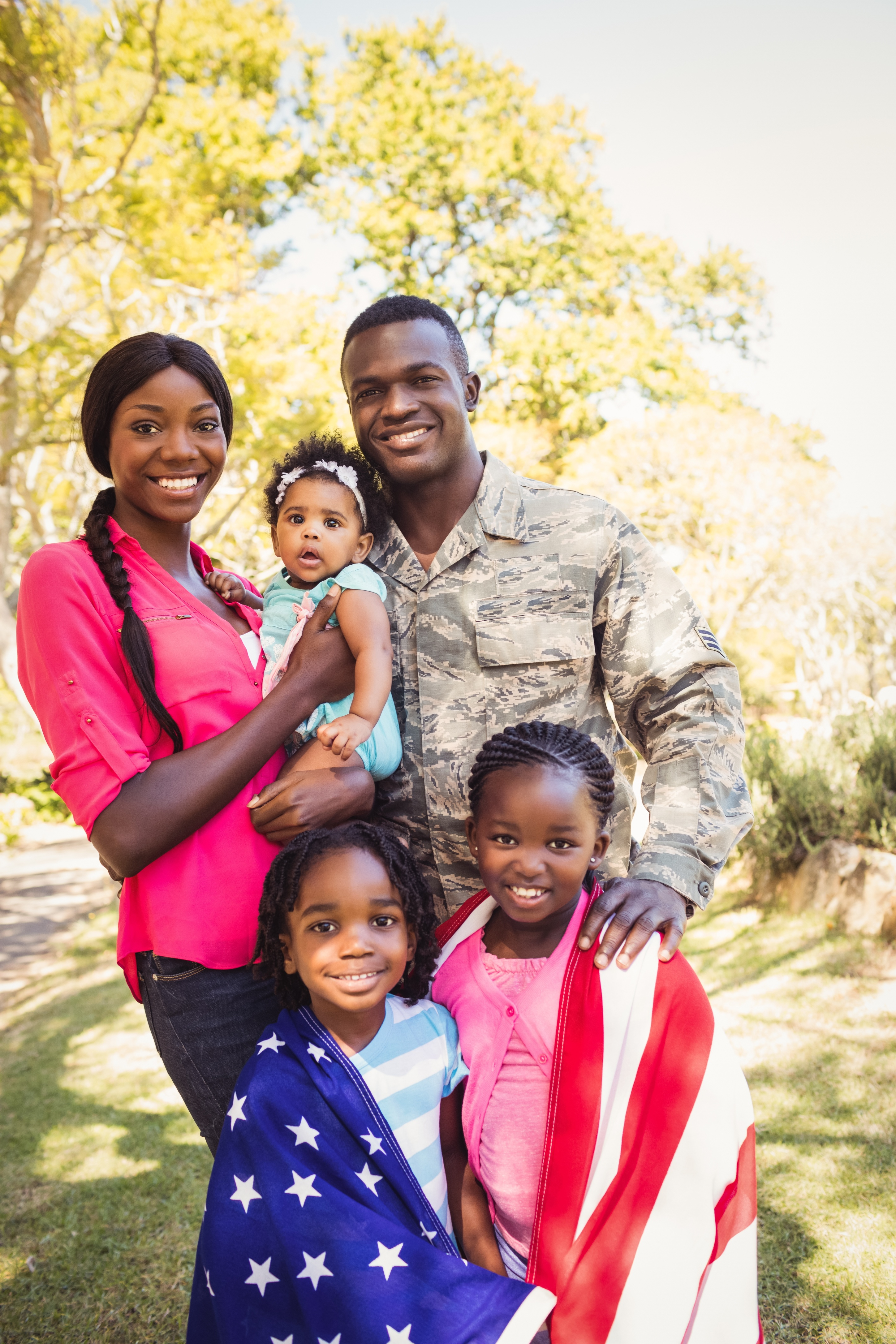 A family, including a father in military dress and two children wrapped in an American flag, smiles at the camera.