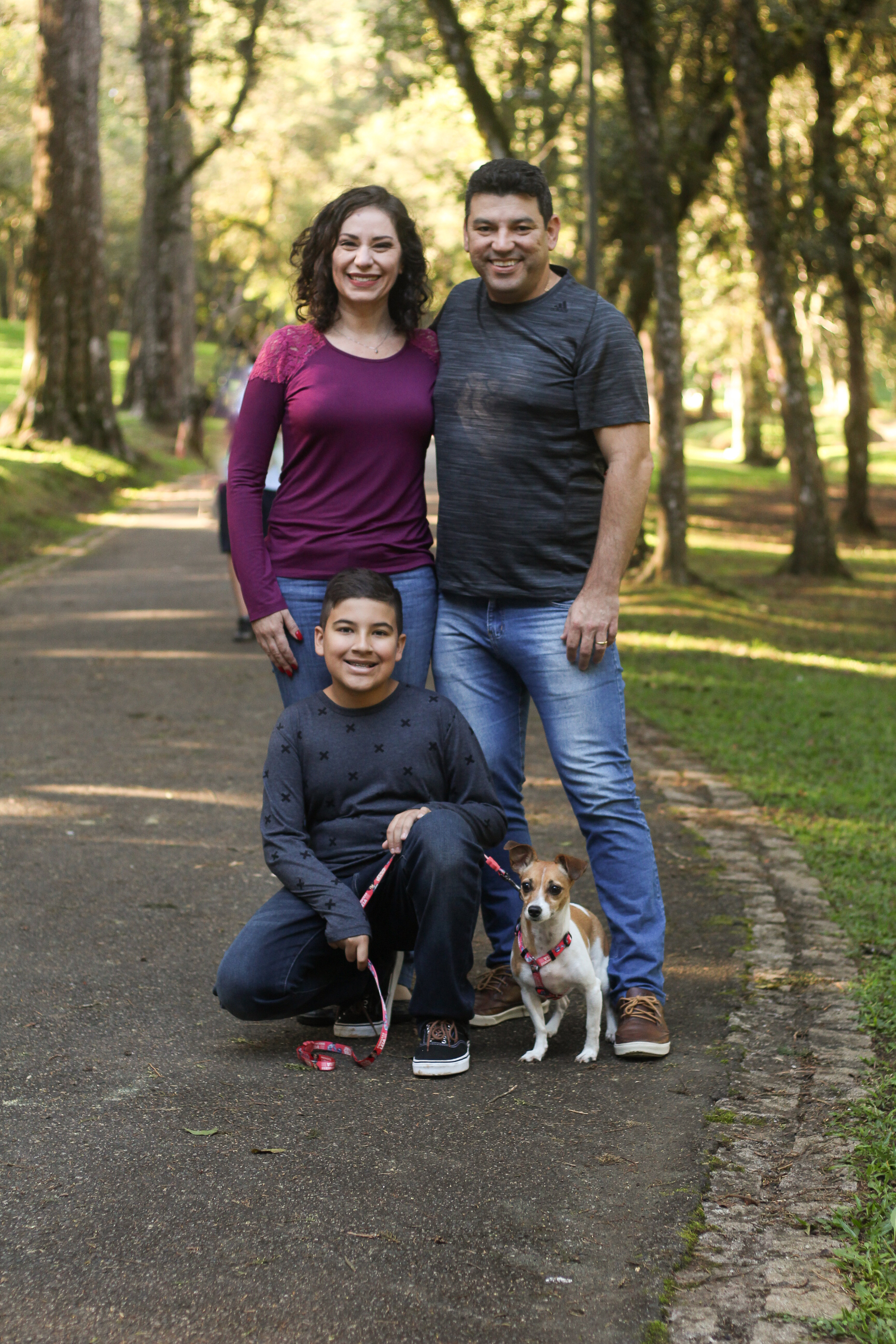 A family stands in a park and smiles at the camera, posing with their dog.