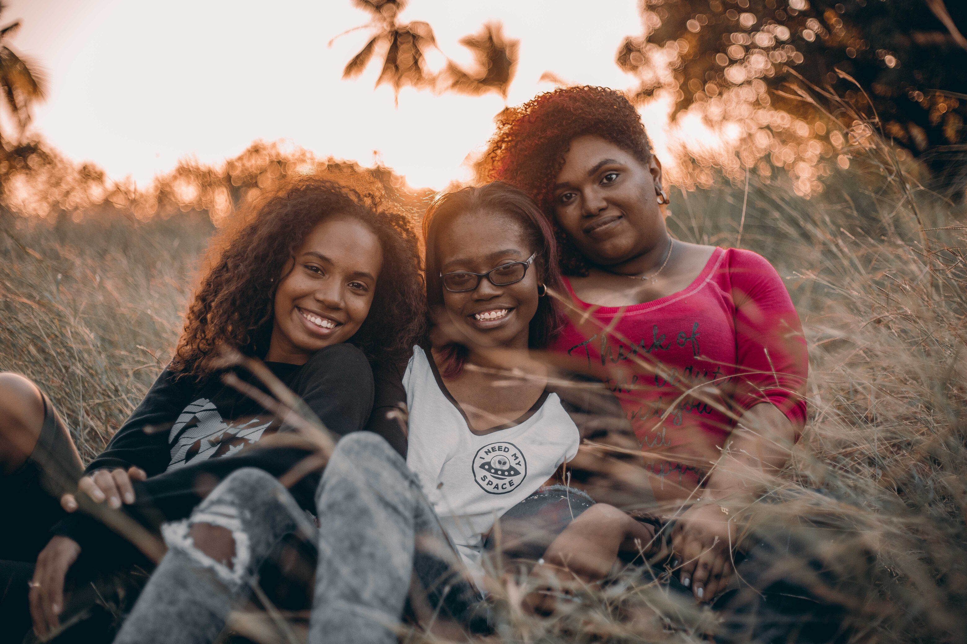 A mother and two daughters sit in a grassy field and smile.