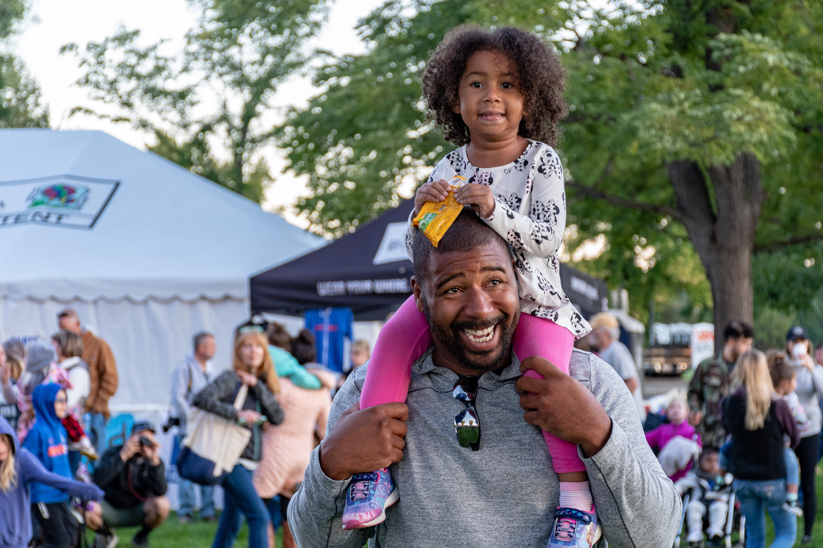 A young girl sits on her father's shoulders at an outdoor community event.
