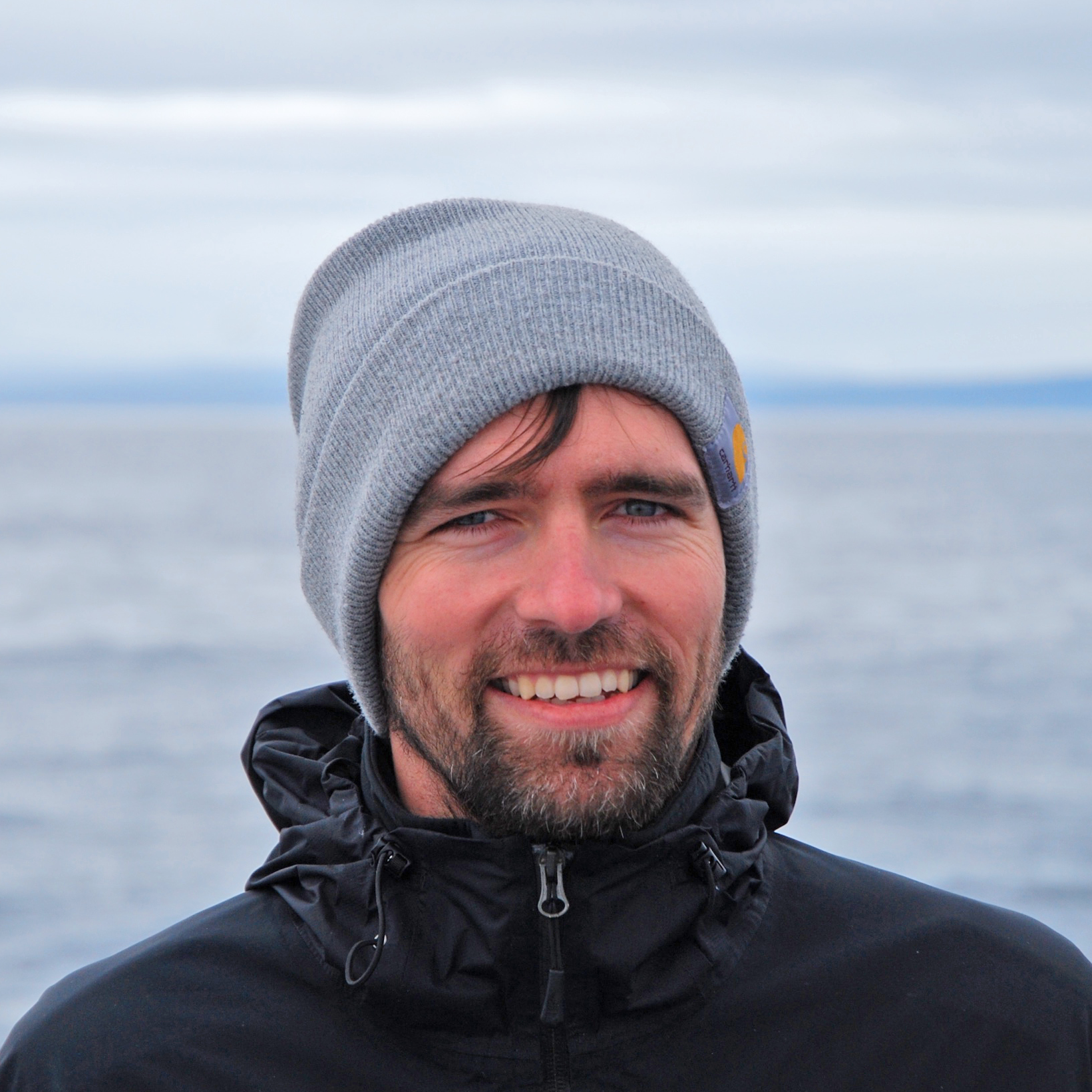 Bart Elmore headshot. Gray beanie. Ocean and gray sky in background.