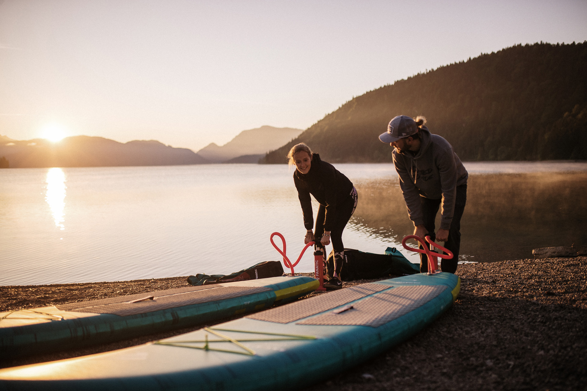 A man and a woman inflating stand up paddleboards near a mountain lake