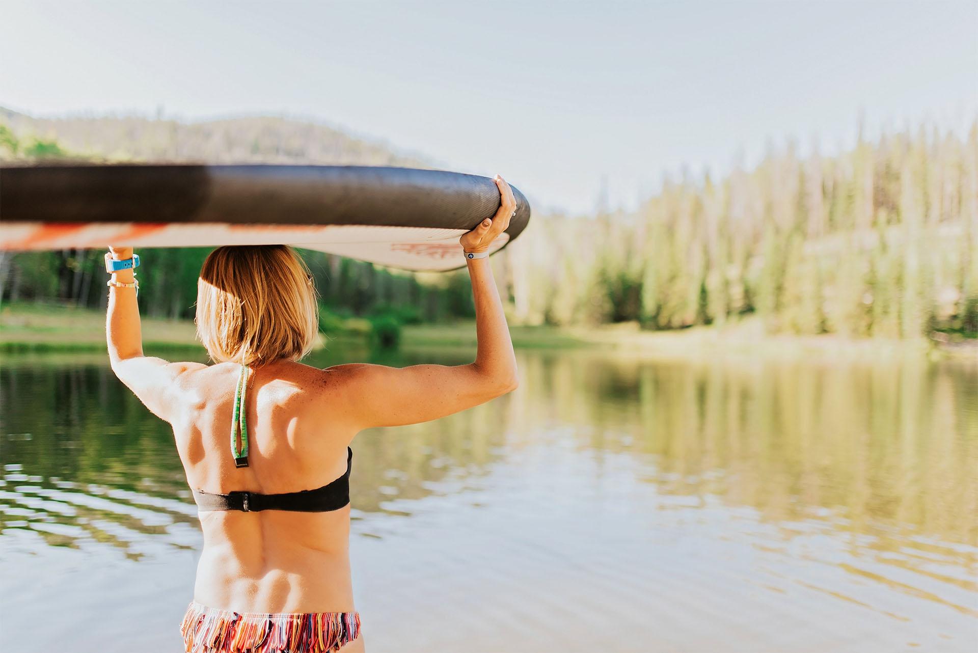 Woman balancing a paddleboard on her head near a mountain lake