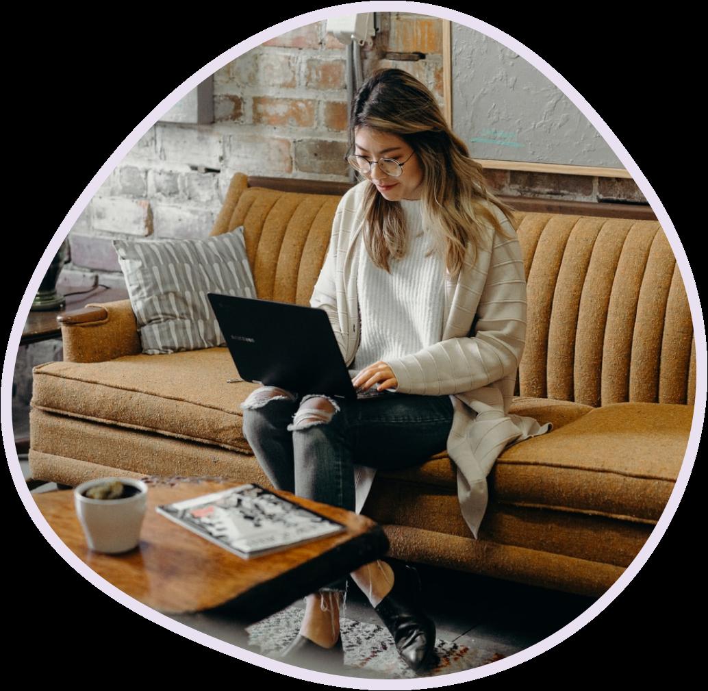 En kvinna som jobbar på en bärbar dator på en soffa