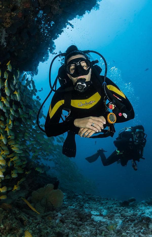 SCUBA exploration with fish near cavern