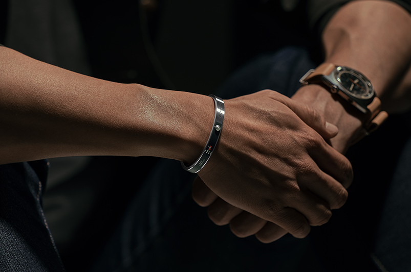 a man with a bracelet, crossing one hand over the other