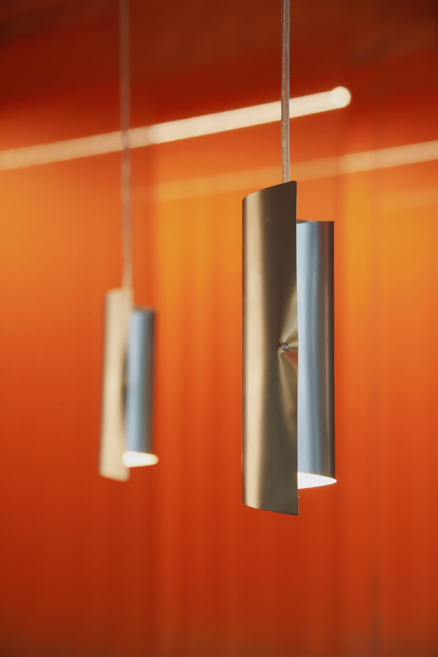 Long designer lamps hanging from the ceiling, with orange curtains in the background.