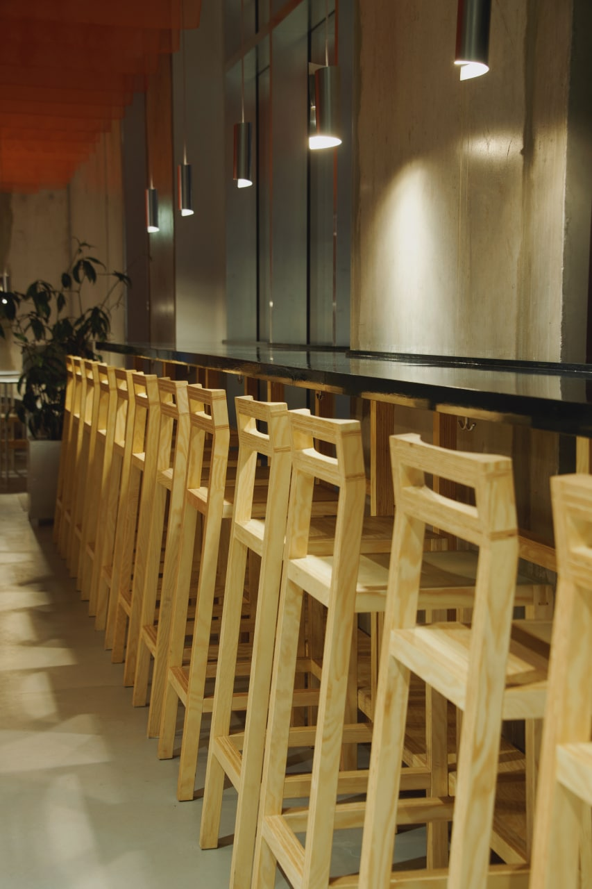 A long serving area with a lot of fine design wooden chairs aligned along the long table.