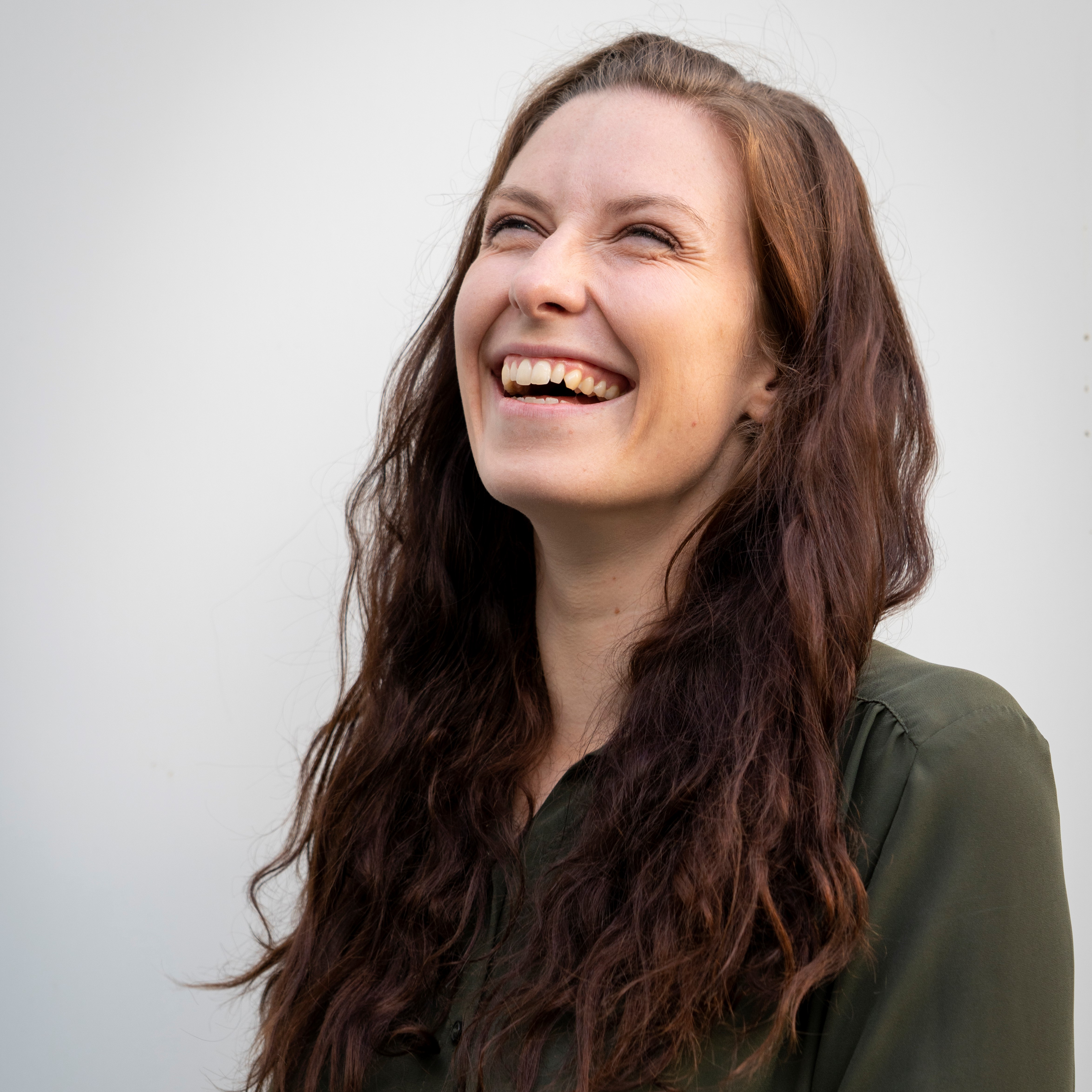 Andrea with long brown hair, looking upwards and laughing