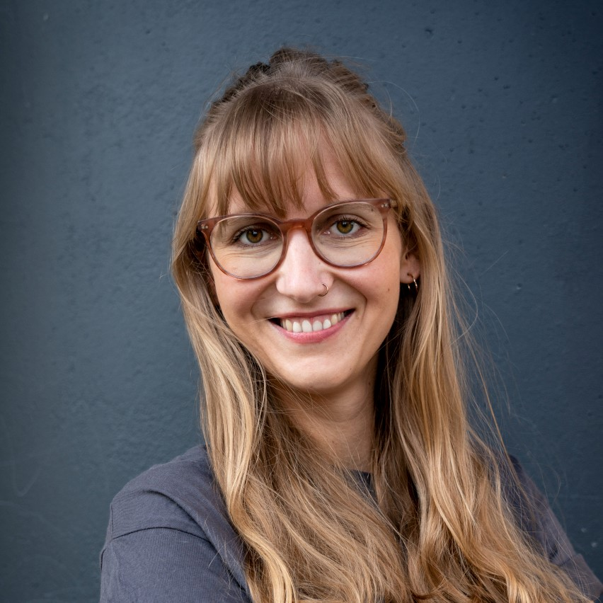 Ines with long dark blonde hair and glasses, standing in front of a deep blue wall