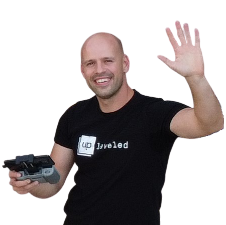 drone picture of Jànos wearing an UpLeveled logo shirt and holding a drone remote control waving at the camera