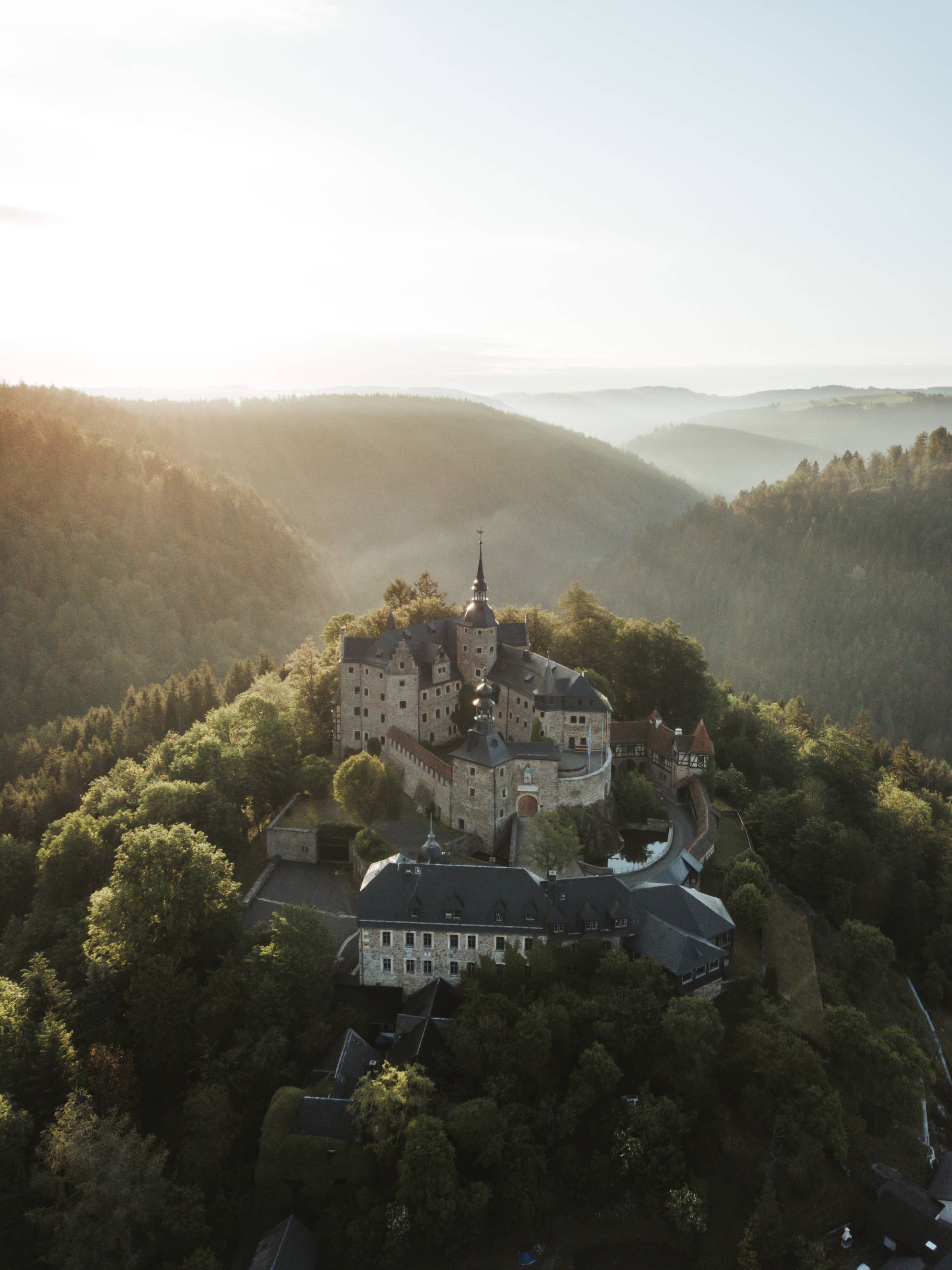 German castle on a hill surrounded by forest while sun rises in the background