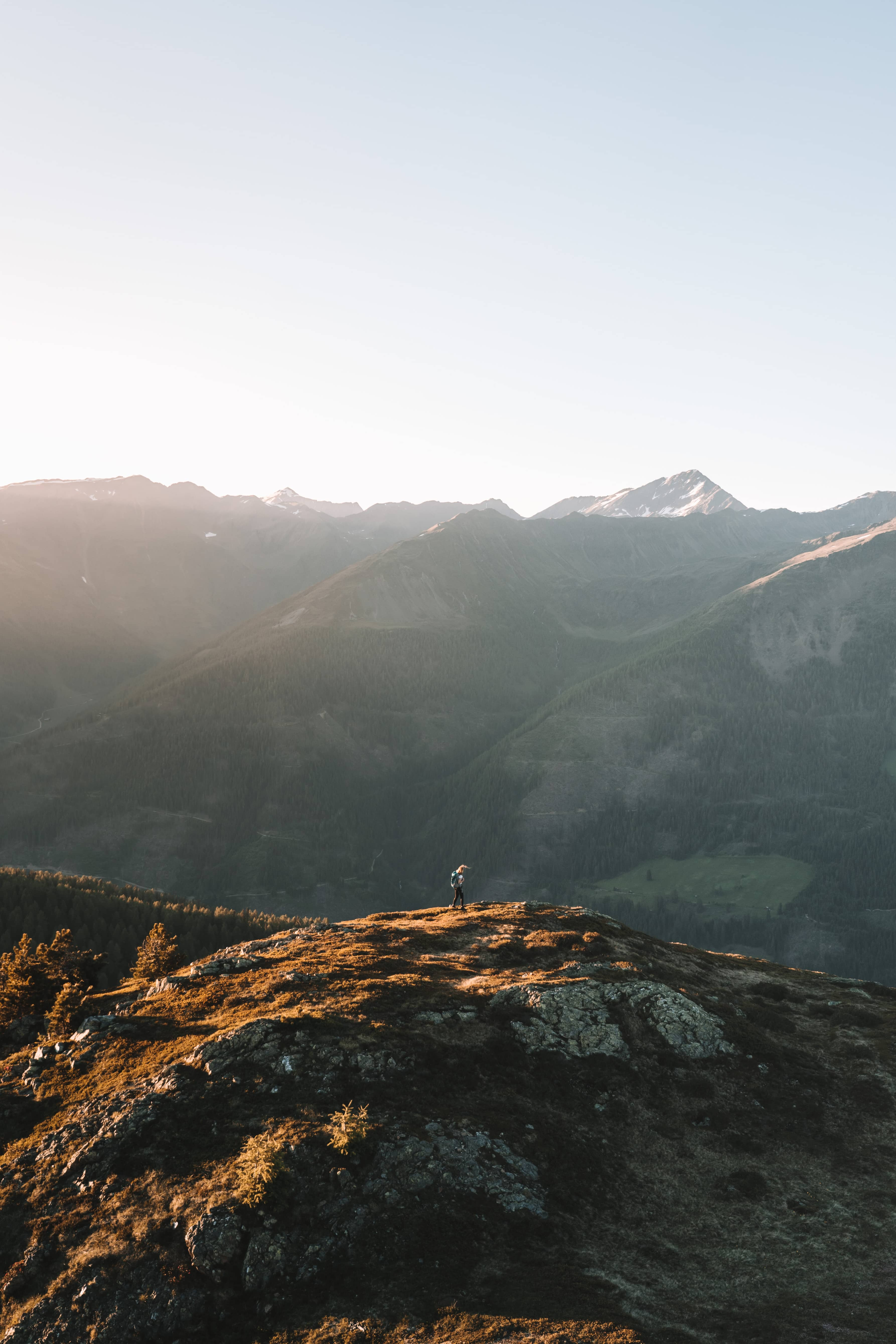 eastern Tyrol mountains while the sun is setting with wanderer hiking on a hill