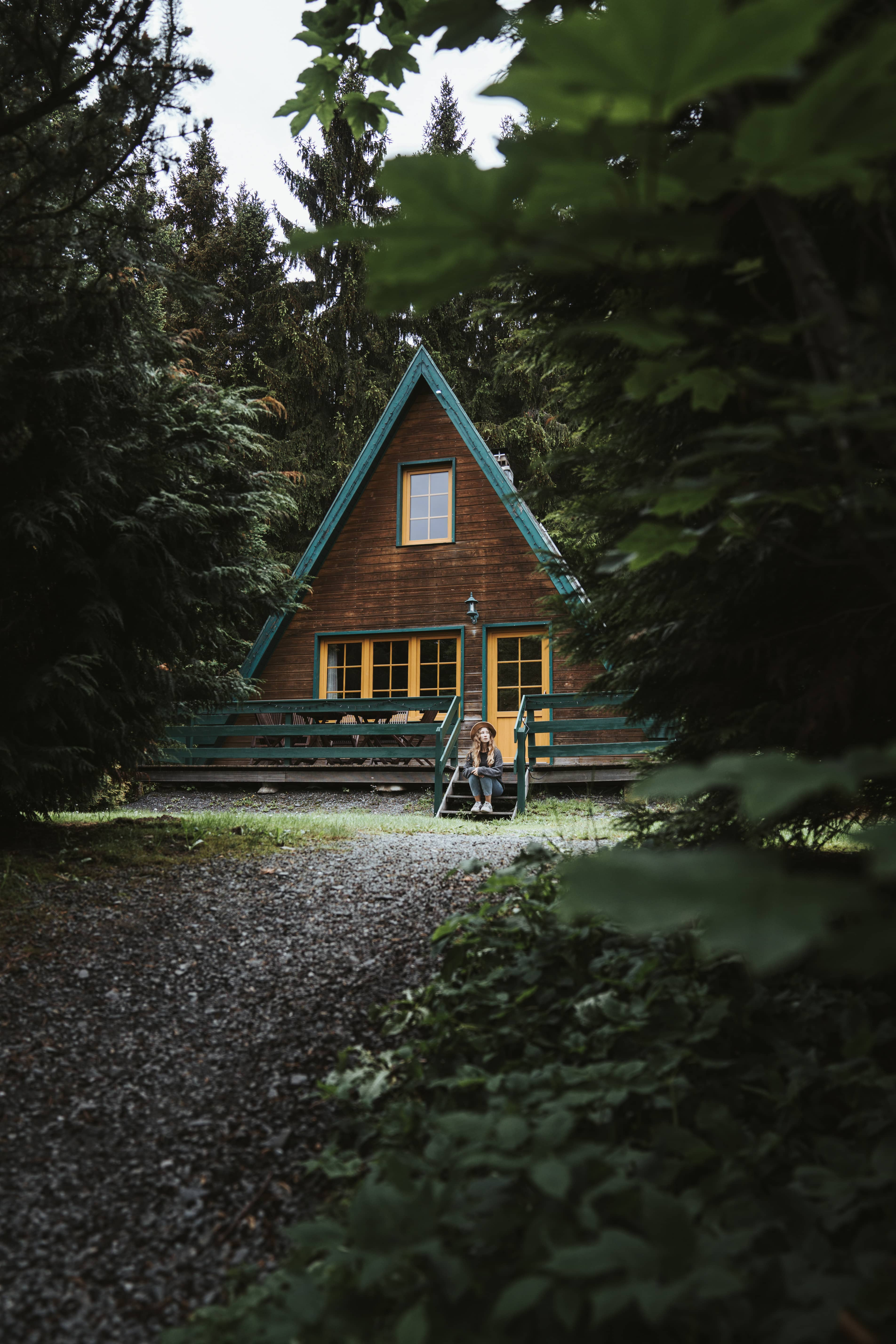 girl in forest sitting in front of small wooden cottage in Thüringen
